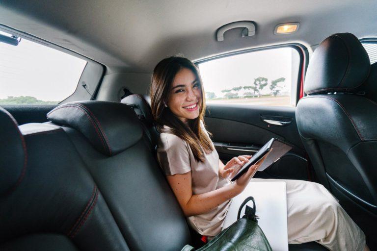 Kvinna som ler i taxi